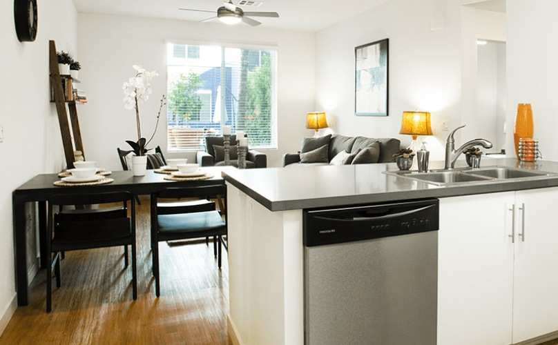 Spacious well lit kitchen with stainless steel appliances and wood floors with access to the living room.