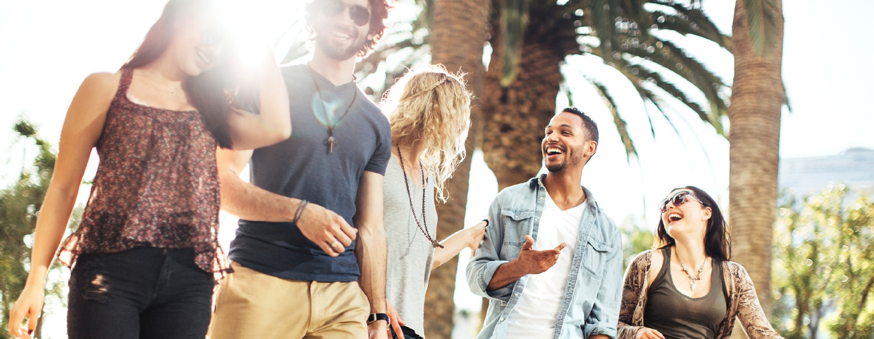 A group of friends hanging out and laughing surrounded by palm trees