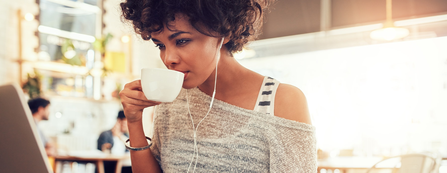Women sitting in a cafe on her computer drinking Coffee